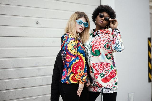 dvě dívky oblečené v barevných mikinách